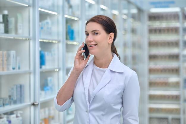 Farmacéutico atractivo complacido hablando por su teléfono inteligente en el interior