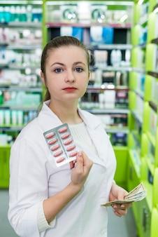 Farmacéutico con blister de píldoras y billetes de dólar