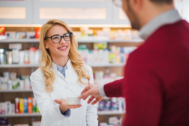 Farmacéutico y cliente en una farmacia.