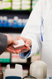 Farmacéutico con cliente que paga en farmacia