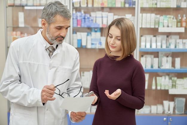 Farmacéutico consulta mujer sobre prescripción en farmacia.