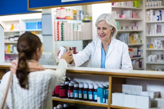 Farmacéutico dando caja de medicina al cliente