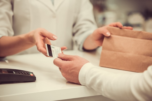 Farmacéutico dando una compra a un cliente y hablando.