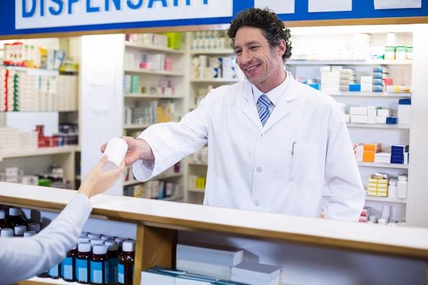 Farmacéutico dando frasco de pastillas al cliente