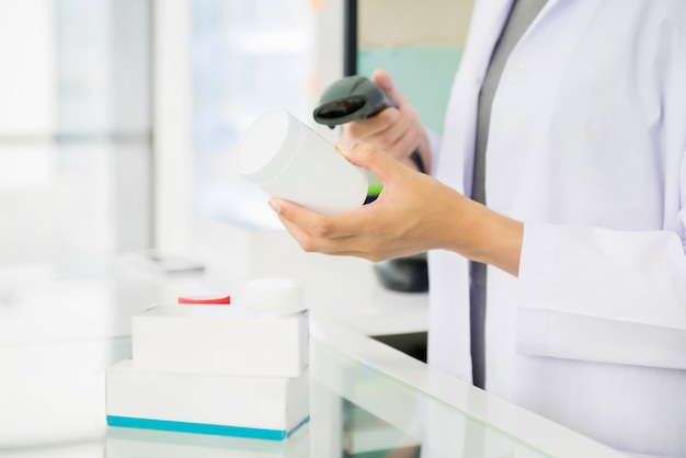 Farmacéutico escaneando frasco de medicina con escáner de código de barras en farmacia
