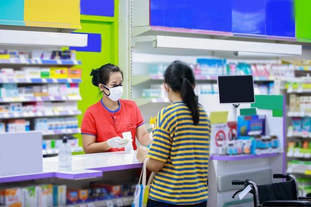 Farmacéutico en mascarilla médica hablando con un cliente en el mostrador de la farmacia