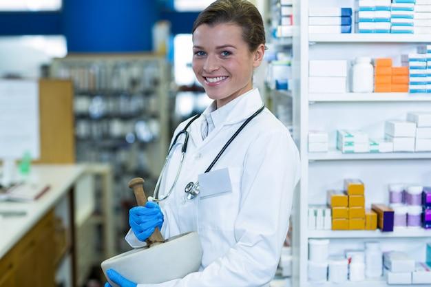 Farmacéutico moliendo medicina en mortal y mortero en farmacia