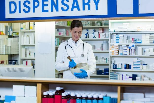 Farmacéutico moliendo medicina en mortal y mortero en mostrador
