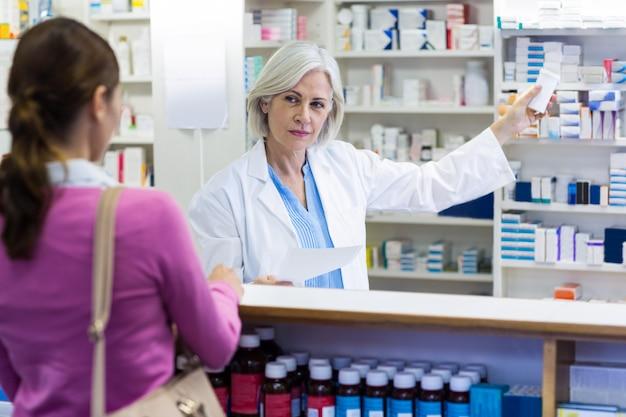 Farmacéutico mostrando la botella de droga al cliente