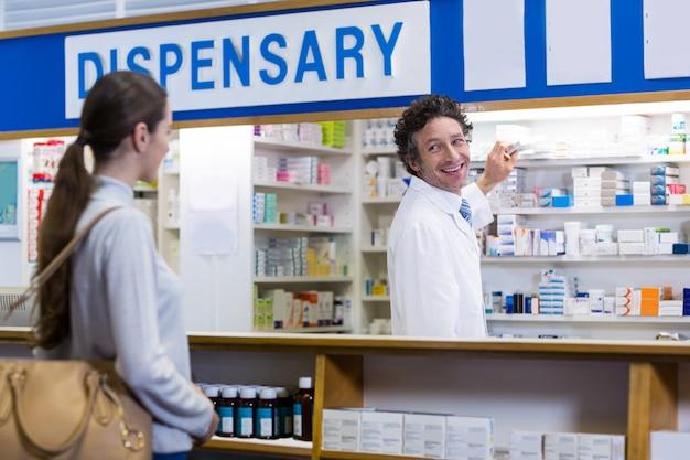 Farmacéutico mostrando la caja del medicamento al cliente