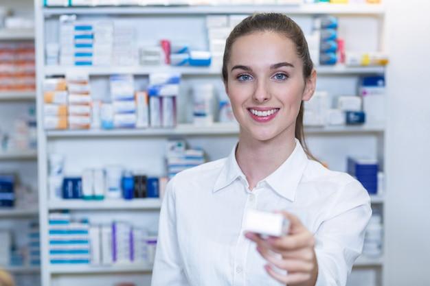 Farmacéutico mostrando un medicamento en farmacia
