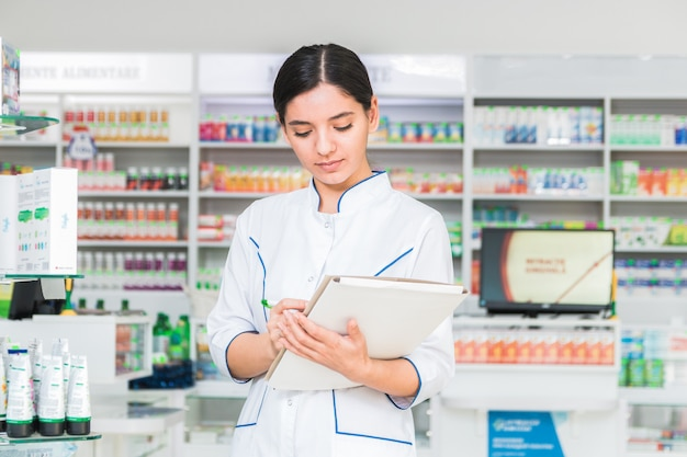Farmacéutico de mujer inteligente y segura sosteniendo una carpeta y tomando notas