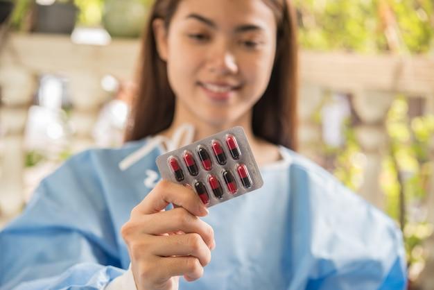 Farmacéutico de la mujer que sostiene la medicina de la prescripción de la orden del doctor