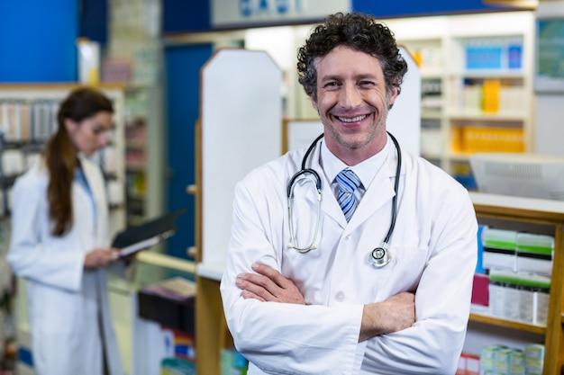Farmacéutico de pie con los brazos cruzados en farmacia