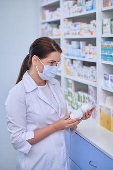 Farmacéutico de pie ante los estantes con medicamentos
