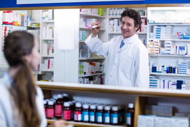 Farmacéutico de pie en el mostrador y mostrando la caja de medicamentos