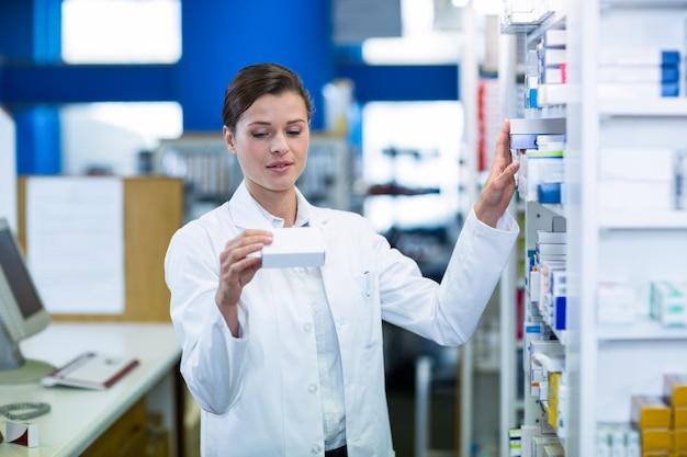 Farmacéutico que controla la medicina en estante