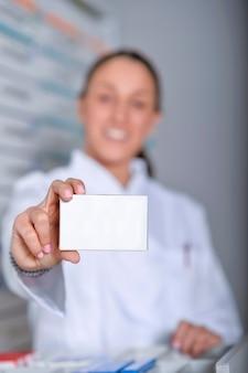 Farmacéutico que muestra la caja de la medicina en blanco blanco con estantes de tiendas de farmacia