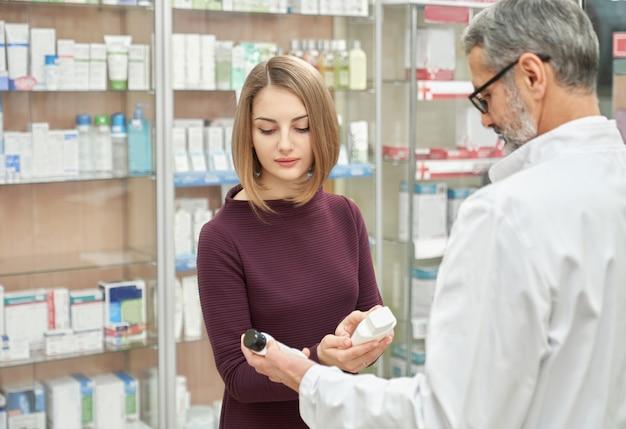 Farmacéutico que ofrece productos cosméticos al cliente.