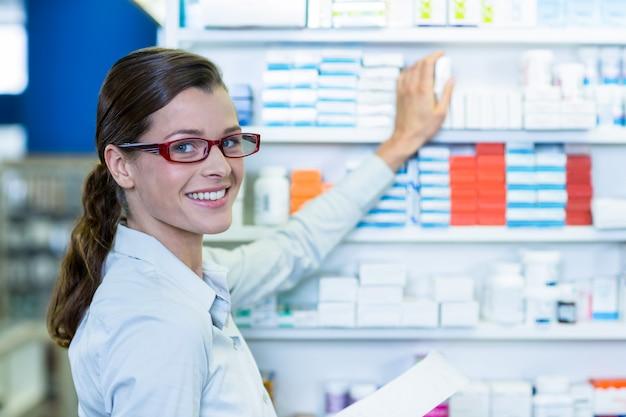 Farmacéutico con receta mientras revisa el medicamento en farmacia