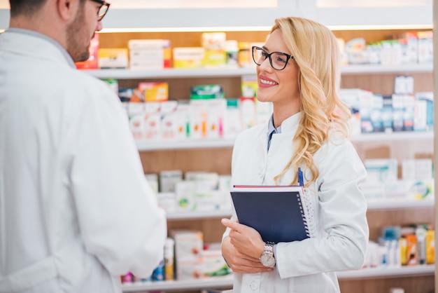 Farmacéutico de sexo femenino joven hermoso que habla con su compañero de trabajo masculino.