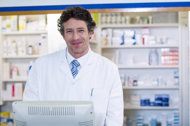 Farmacéutico sonriente de pie en el mostrador en farmacia