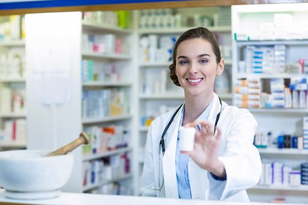 Farmacéutico sonriente que muestra el envase de la medicina en farmacia
