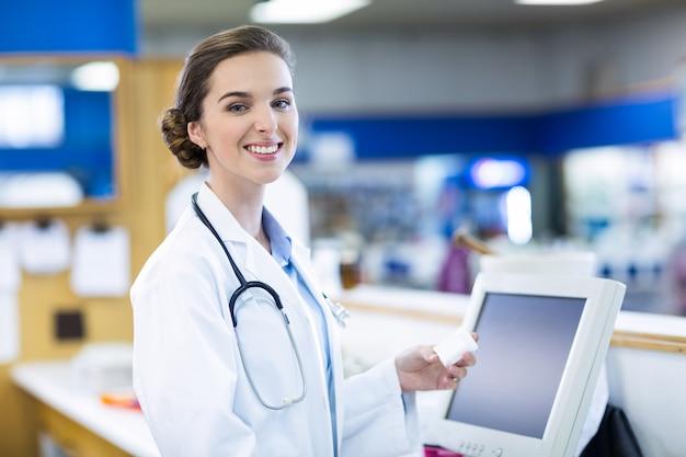 Farmacéutico sonriente que sostiene el envase de la medicina en farmacia