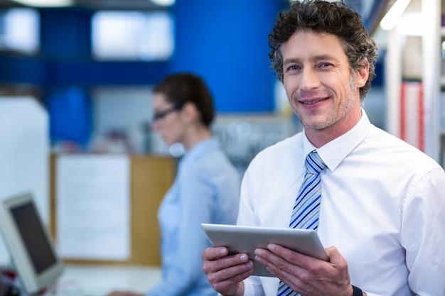 Farmacéutico sonriente que sostiene la tableta digital en farmacia