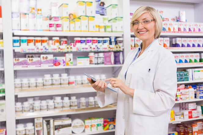 Farmacéutico sonriente que usa la pc de la tableta