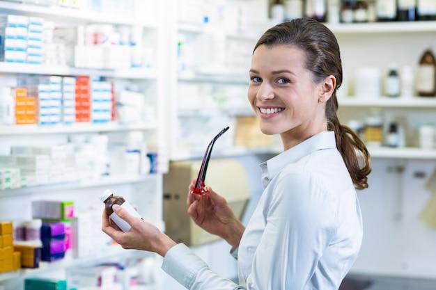 Farmacéutico sosteniendo una botella de medicamento en farmacia