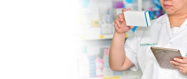 Farmacéutico sosteniendo la caja de la medicina y el panel táctil para la barra de búsqueda en la pantalla de la farmacia