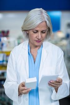 Farmacéutico sosteniendo medicamentos mientras verifica la prescripción