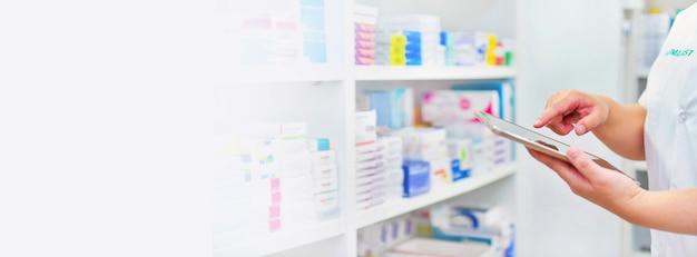 Farmacéutico sosteniendo la tableta de la computadora canta para llenar la receta en la farmacia farmacia