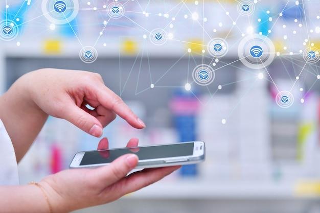 Farmacéutico con un teléfono inteligente para surtir recetas en pharmacydrugstore