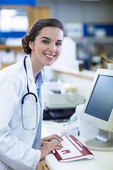 Farmacéutico trabajando en computadora en farmacia