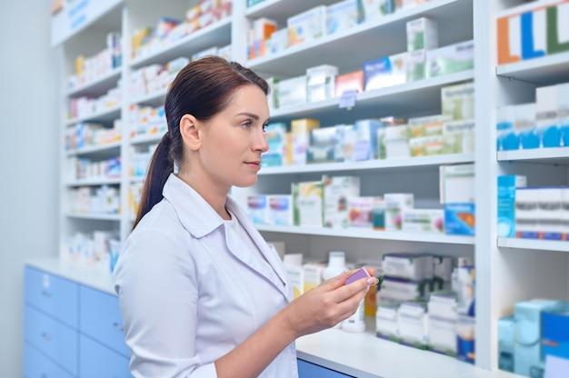 Farmacéutico tranquilo pensativo de pie ante un estante con medicamentos