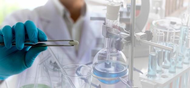 El farmacéutico está utilizando una pinza para llevar el medicamento a examinar en el laboratorio.