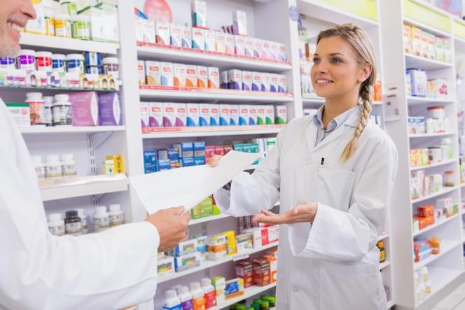 Farmacéutico y aprendiz hablando juntos sobre la medicación