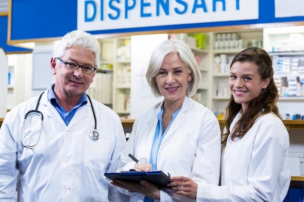 Farmacéuticos escribiendo en portapapeles en farmacia