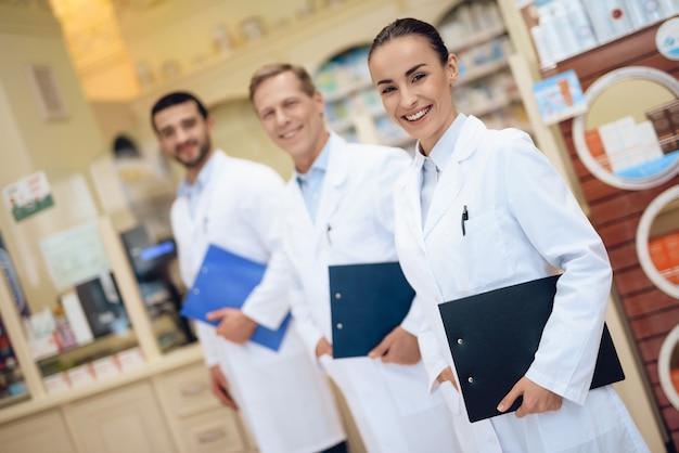 Los farmacéuticos están en la farmacia y tienen carpeta con papeles.