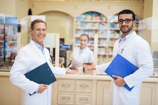Los farmacéuticos se paran en la farmacia y sostienen la carpeta.