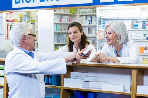 Farmacéuticos de pie en el mostrador e interactuando entre sí