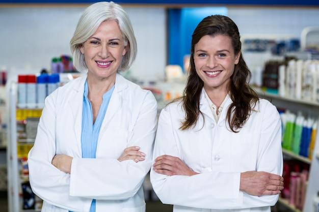 Farmacéuticos sonrientes de pie con los brazos cruzados en farmacia