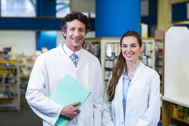 Farmacéuticos sonrientes que se colocan con el archivo en farmacia