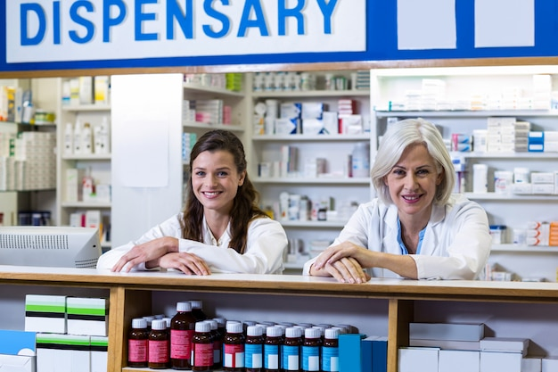 Farmacéuticos sonrientes que se colocan en el mostrador en farmacia