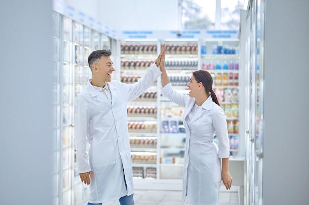 Farmacéuticos en túnicas blancas saludándose en el lugar de trabajo