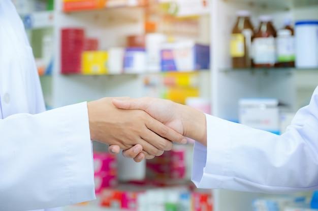 Farmacia del farmacéutico que da la mano a un cliente en la farmacia, concepto de salud