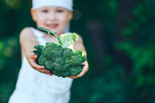 Farmer boy en overoles blancos y diadema gris mostrando brócoli orgánico fresco en el jardín