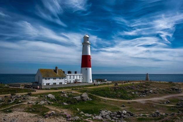Faro blanco y rojo en la orilla cerca del mar bajo un cielo impresionante